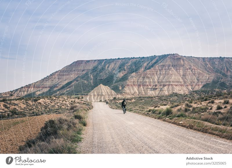 Man riding bicycles on road in desert hills Bicycle Street Desert Hill Landscape Sand Stone Plant Trip Dry Nature Sky Vacation & Travel Hot Destination