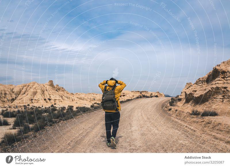Man walking on road in desert hills Street Desert Hill Landscape Sand Stone Plant Trip Dry Nature Sky Vacation & Travel Hot Destination exploring