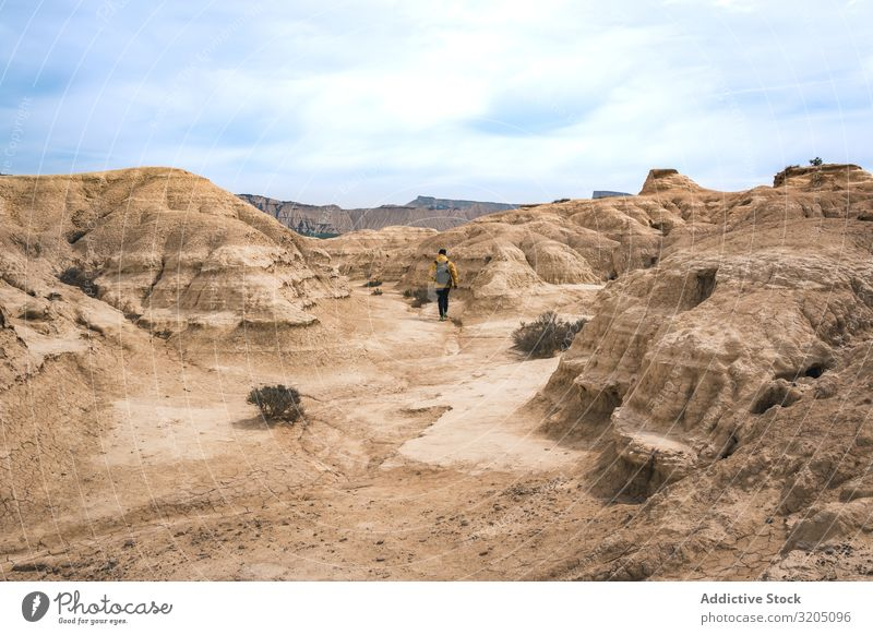 Man walking on amazing landscape of desert hills on background of blue sky Desert Hill Landscape Sand Stone Plant Trip Dry Nature Sky Vacation & Travel Hot