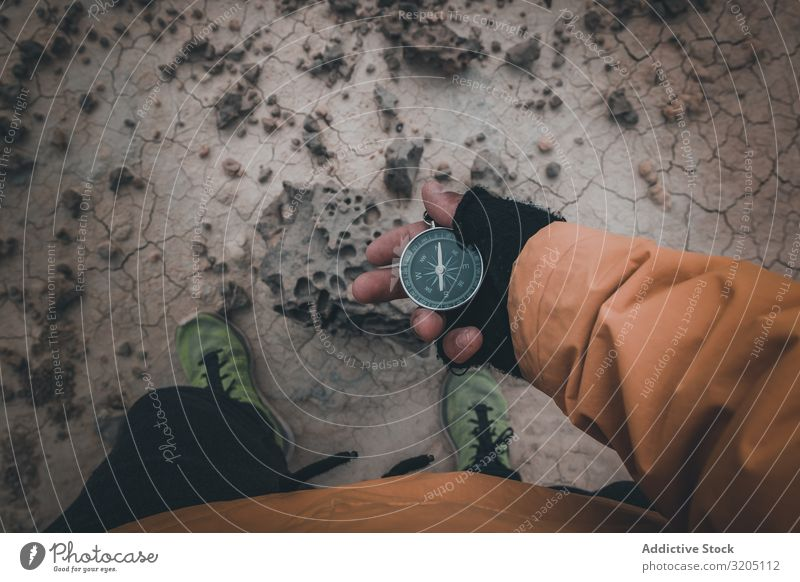 Compass in hand on dry desert area Compass (drafting) Direction Desert Equipment Orientation Sand Adventure Vacation & Travel exploration Geography Magnetic