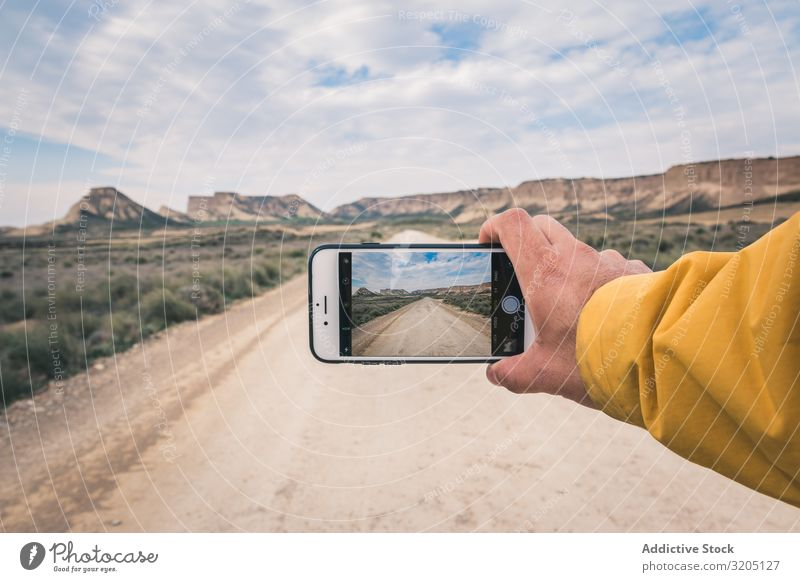Person taking picture of empty road and desert landscape Man Street taking photo Desert Hill Landscape Sand Stone Plant Trip PDA Dry Nature Sky