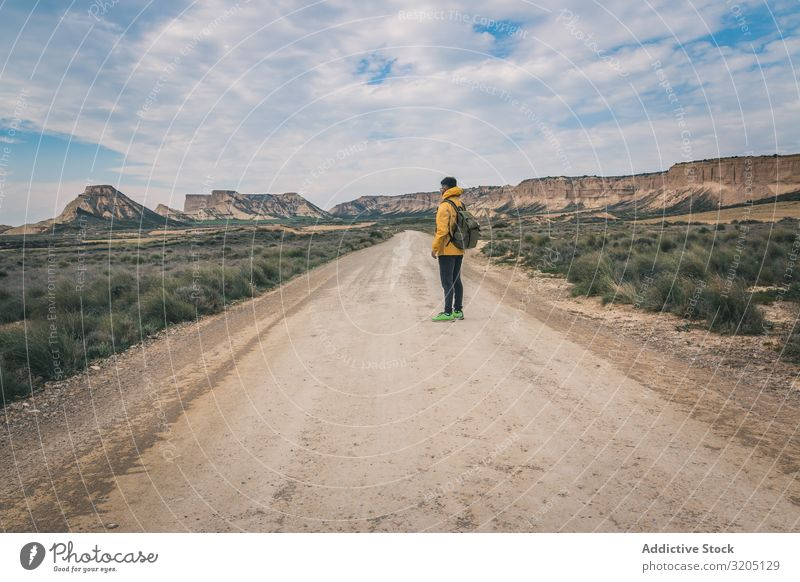 Man standing on road in desert hills Street Desert Hill Landscape Sand Stone Plant Trip Dry Nature Sky Vacation & Travel Hot Destination exploring