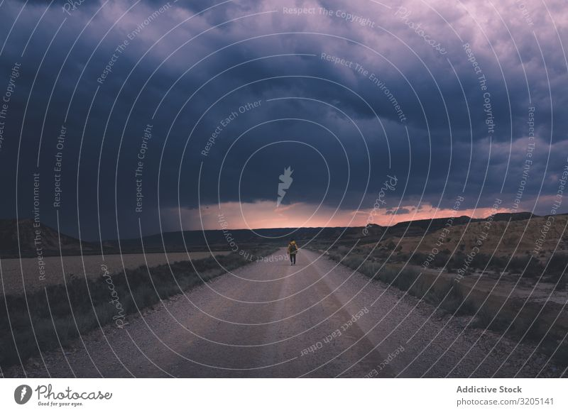 Man standing on road and looking at impressive evening sky Street Twilight Desert Landscape Sand Stone Trip Dusk Nature Sky Vacation & Travel Hot Destination