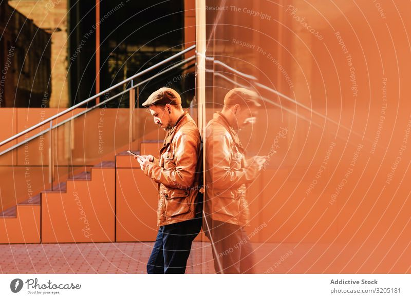 Man using mobile phone in modern building Self-confident Wall (building) Lean Building Style Sunbeam Day Youth (Young adults) Easygoing Hip & trendy Success