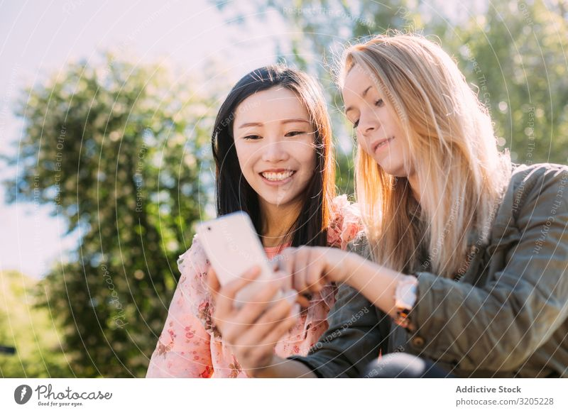 Female friends using smartphone in park Friendship PDA Park Indicate Smiling Mixed race ethnicity Woman Youth (Young adults) Share Together Lifestyle