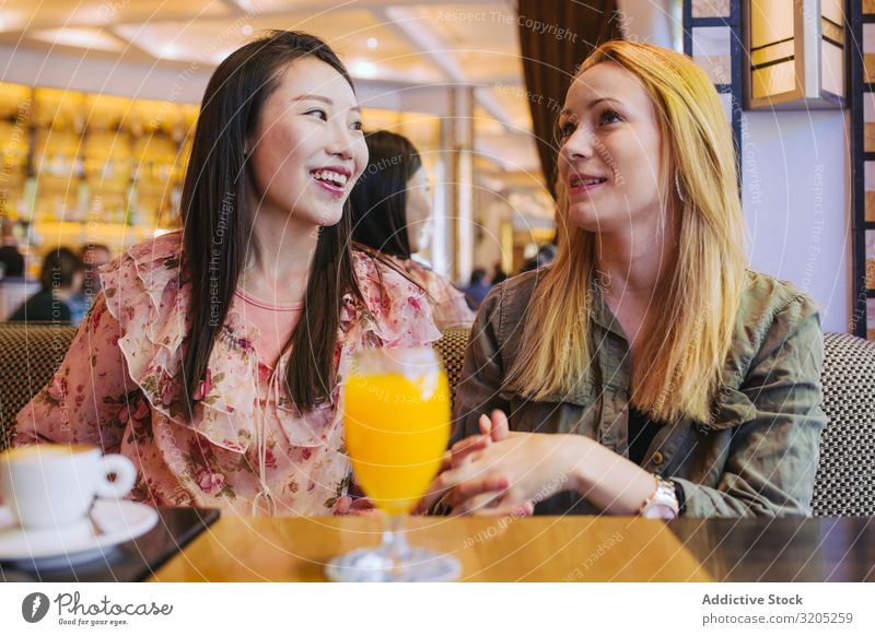 Multiethnic friends talking in cafe Friendship Café speaking Together Woman Youth (Young adults) Mixed race ethnicity Smiling Sit Table Lifestyle