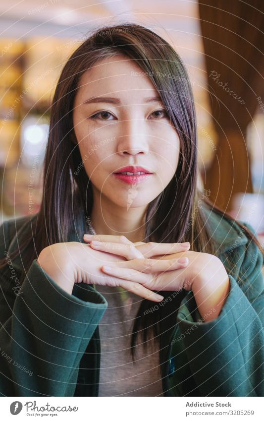 Portrait of young asian woman looking at camera Woman Café Table Sit Youth (Young adults) Looking into the camera approachable To enjoy Lifestyle