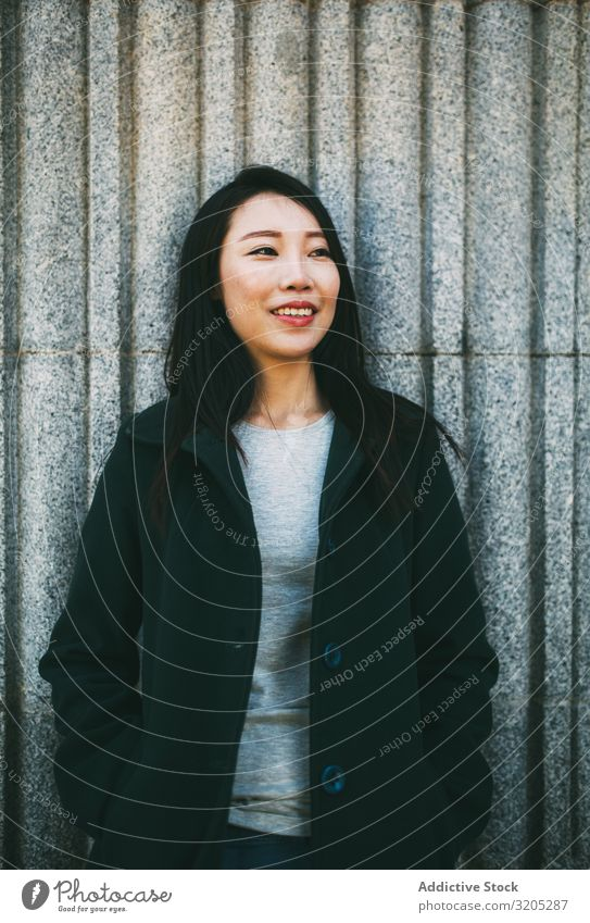 Asian woman near marble wall Woman Wall (building) Lean asian Smiling Youth (Young adults) Street City Marble Building Elegant Coat Style Hip & trendy Easygoing