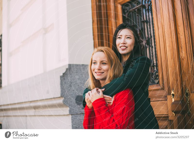 Cheerful female friends hugging near ornamental door Friendship Embrace Smiling Looking away Door Street Building City Mixed race ethnicity Together Woman