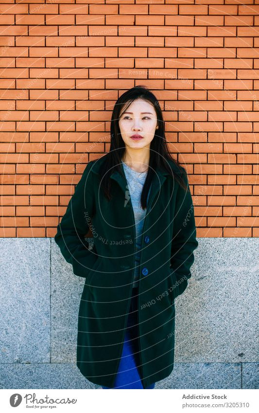 Pensive Asian woman leaning on brick wall Woman Wall (building) Lean Looking away Street City asian Ethnic Rough Relief Surface Lifestyle Leisure and hobbies