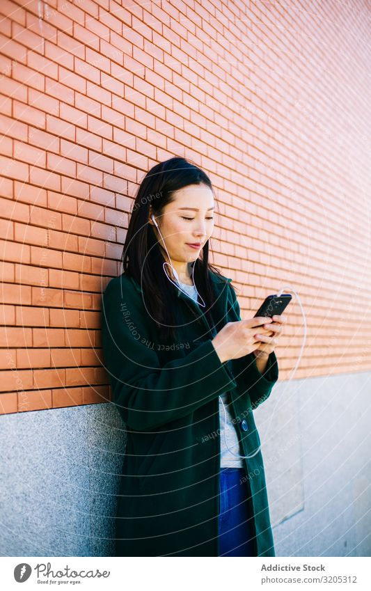 Asian female listening to music near brick wall Woman Listening Music PDA using Wall (building) Lean Brick Street City asian Ethnic Lifestyle