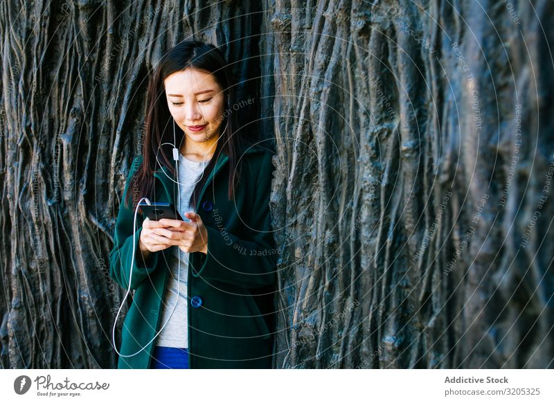 Asian female listening to music near rough wall Woman Listening Music PDA using Wall (building) Lean Root Tree Street City asian Ethnic Rough Relief Surface