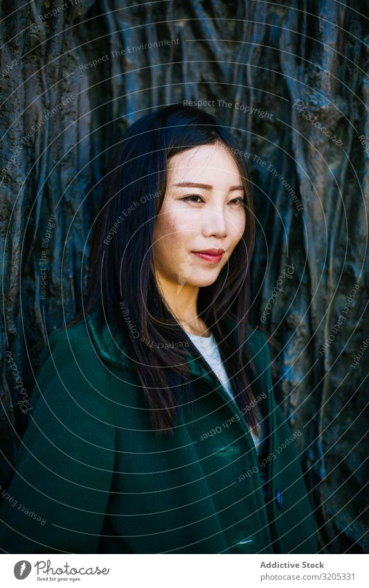 Pensive Asian woman leaning on rough wall Woman Wall (building) Lean Looking away Root Tree Street City asian Ethnic Rough Relief Surface Lifestyle