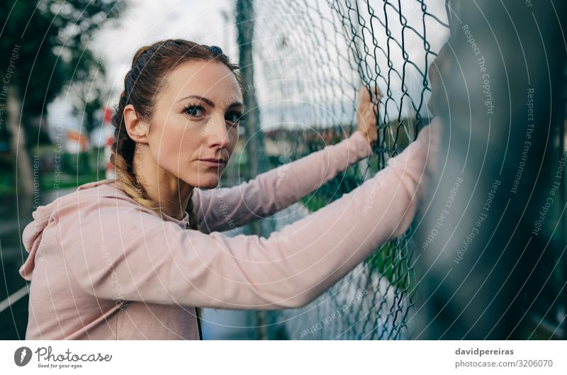 Sporty girl resting on sports court fence Lifestyle Beautiful Body Leisure and hobbies Sports Human being Woman Adults Clouds Rain Fitness Authentic