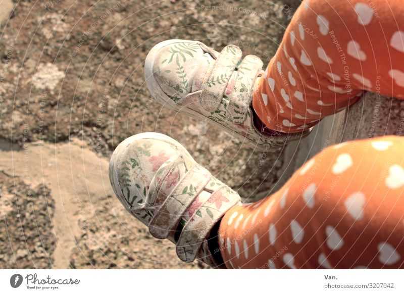 walking in my shoes Child Girl Legs Feet 1 Human being Wall (barrier) Wall (building) Pants Footwear Sit Orange Heart Floral Pattern Stone Ground Colour photo