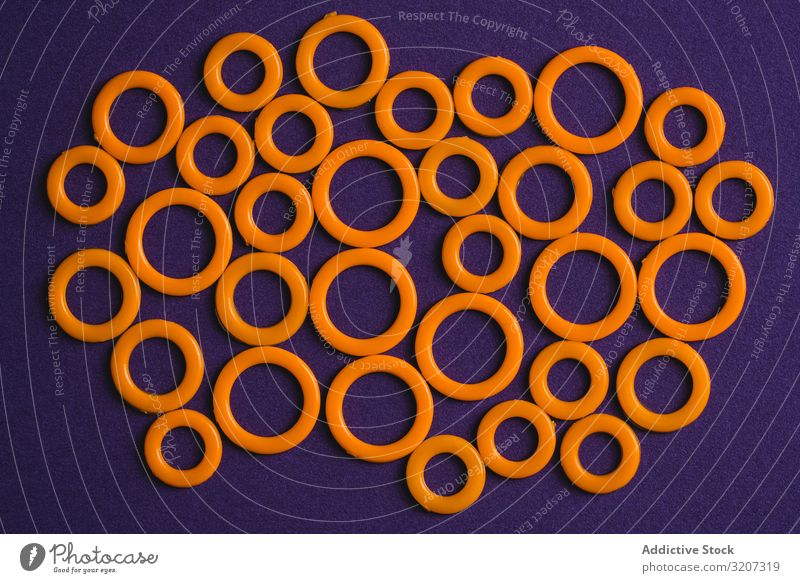 Colorful plastic rings on purple surface circle colorful modern creative bright beautiful art minimal fantasy texture background shape design abstract element