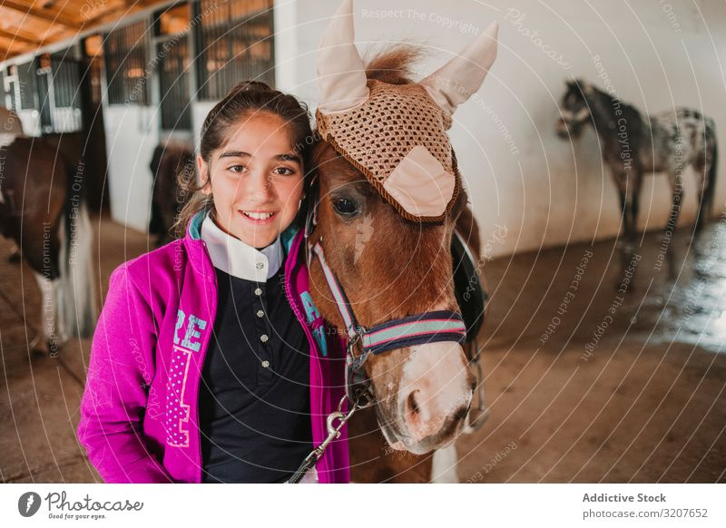 Girl with adorable pony in hat girl stable animal looking at camera child portrait embrace friend pet childhood countryside stroke little cute charming kid farm