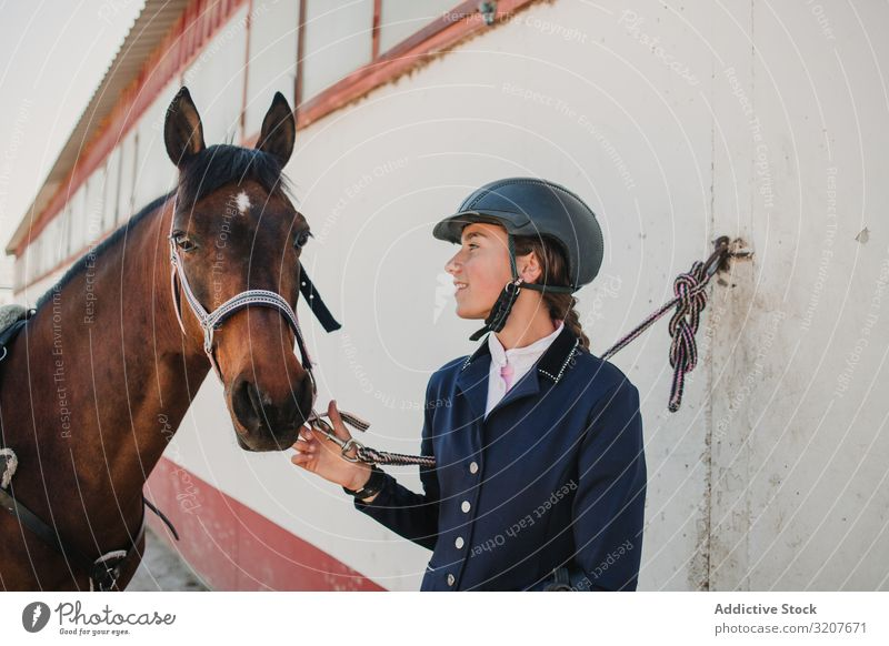 Woman in jockey outfit standing with horse woman stroke animal equestrian teen young pet friend love caress helmet touch beautiful mammal relationship stable