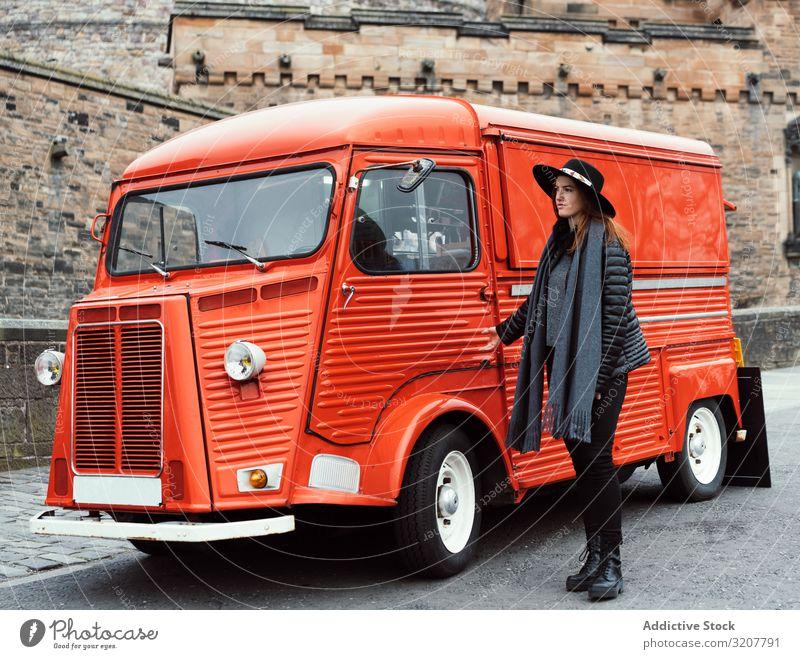 woman walking passing a vintage red van retro female aged style street scotland vehicle tourism redhead truck destination medieval urban vacation horizontal