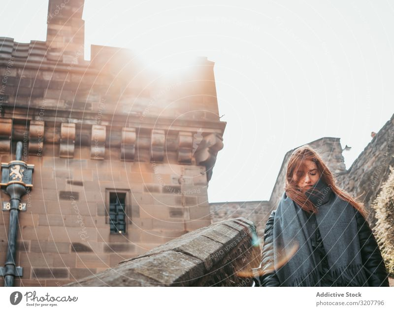 Stylish woman walking in aged medieval building travel old town scotland tourist street style explore architecture city tourism black trendy heritage exterior