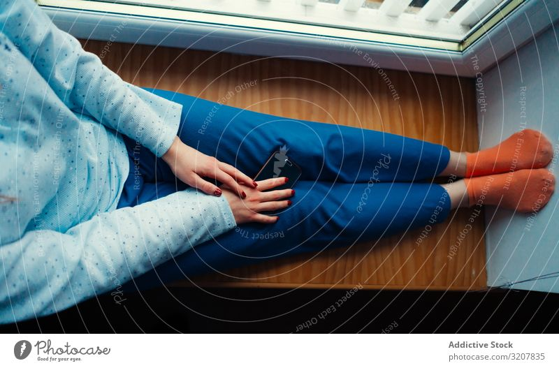Crop woman in home clothes on window sill comfort cozy smartphone colorful scotland sitting relax lifestyle beauty candid beautiful leisure apartment device