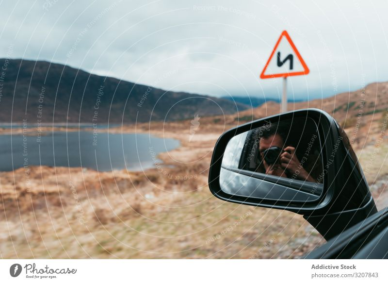 Traveling photographer with camera in car man travel photography mirror landscape scotland self transport lake mountain remote automobile journey window vehicle