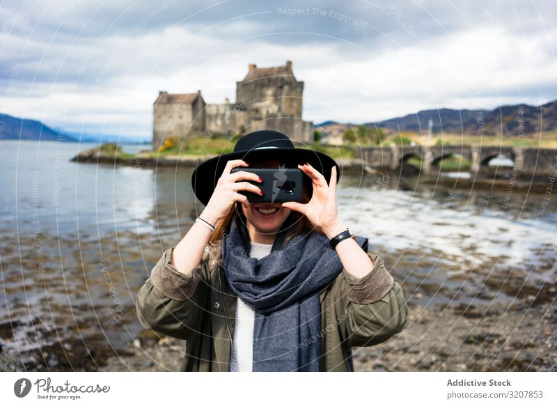 Smiling traveling woman photographing with phone scotland taking photo smartphone nature aged castle old cost photography lake trendy using tourism carefree