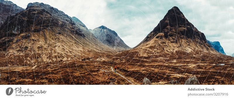 Person walking through picturesque mountains person wind scotland nature cold landscape travel view valley beauty freedom adventure trekking natural tourism