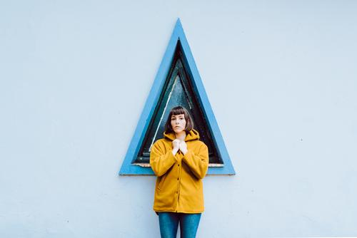 Cheerful female near triangle window woman smile building wall gray young happy standing coat casual jacket warm cheerful joy exterior geometric shape glad lady