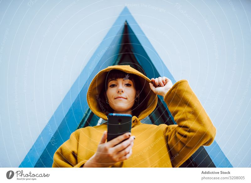 Woman with smartphone against triangle window woman using adjust hood building wall gray young female casual jacket warm exterior coat geometric shape lady