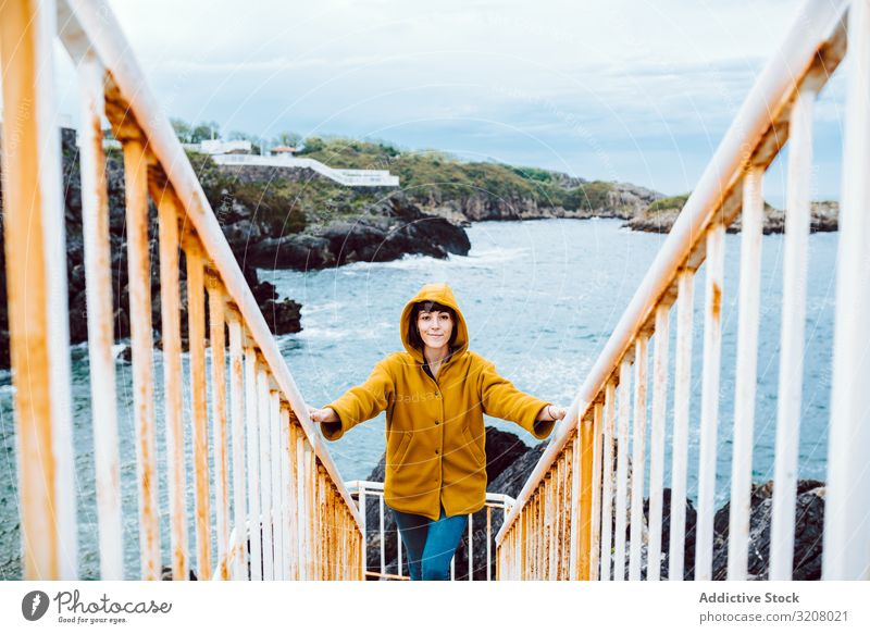 Woman standing on steps near sea woman shore stairway bay waves water rusty railing travel female trip tourism journey casual coast ocean storm weather grungy