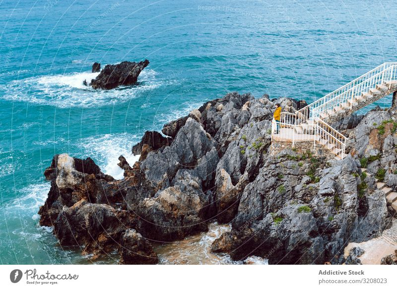 Woman looking at waving sea from steps woman admire waves bay cliff stairway water nature shore female travel trip journey tourism view ocean storm weather