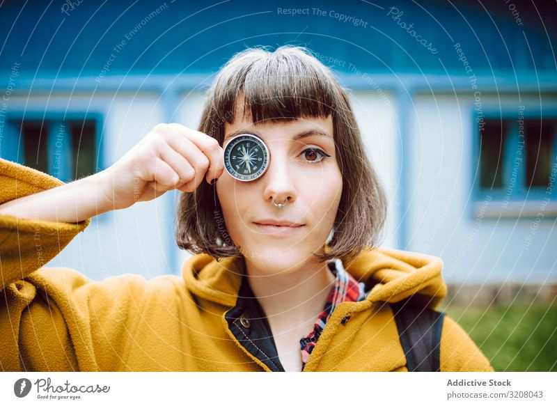 Funny woman with compass near eye crossed eyes funny grimace navigation retro smiling adventure tourism guidance house female vintage tool face expression