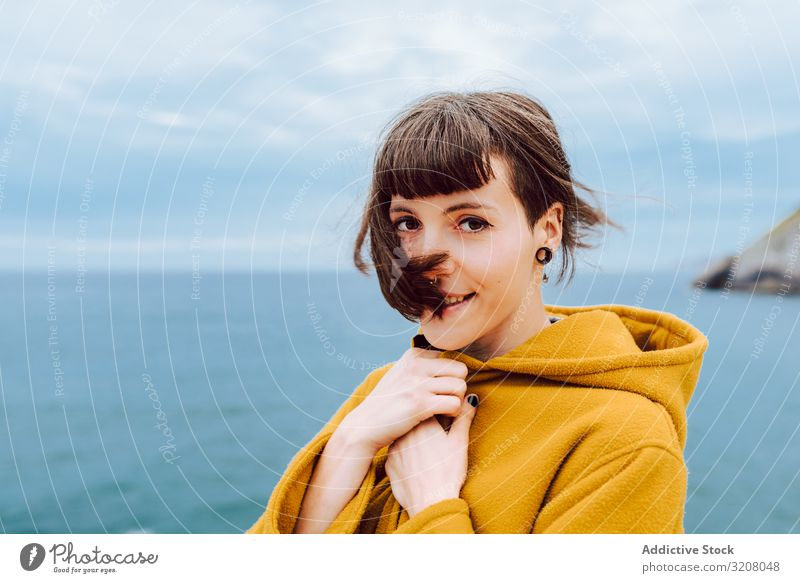 Young woman standing near sea cloudy sky travel jacket warm nature leisure lifestyle female shore coast water ocean blue young trip journey tourism lady glad