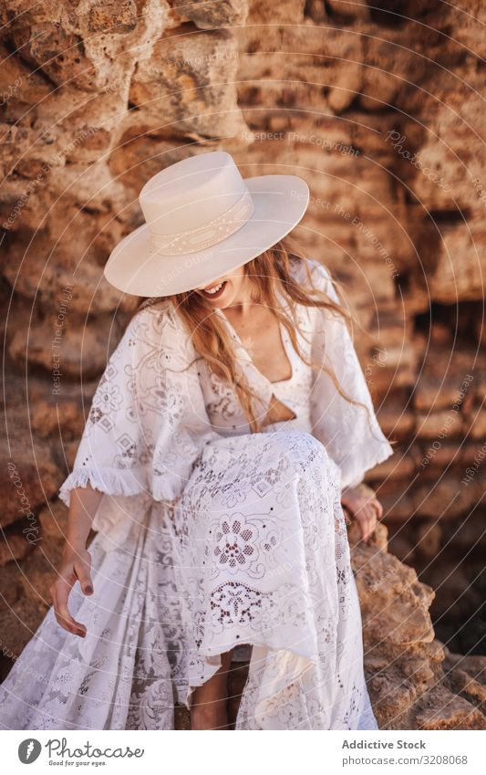 Gorgeous female sitting by ruined wall woman fashion stylish trendy glamorous model dress white lace clothes stone young person beautiful pretty attractive