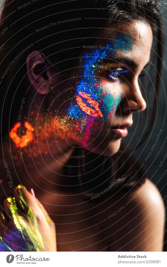 Young woman covered with uv painting young pretty color orange fire black light fluorescent luminous luminescence body art passion body painting looking away