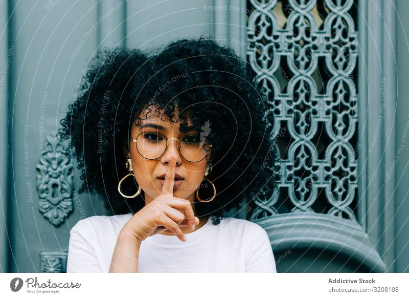 Stylish African American female by green door asking for silence woman threshold stylish trendy casual african american hairstyle ethnic young person serious