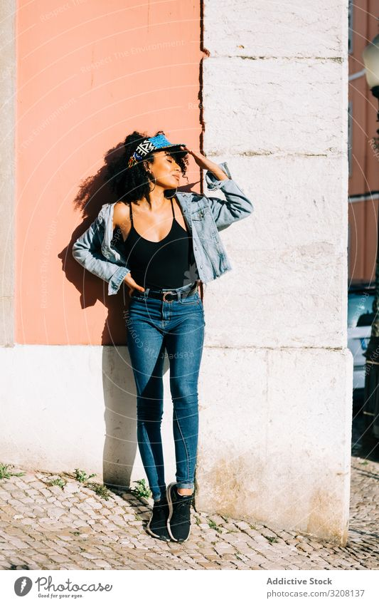 Pretty ethnic female leaning on wall and holding head woman fashion stylish trendy clothing glamorous outfit headband jeans denim young african american casual