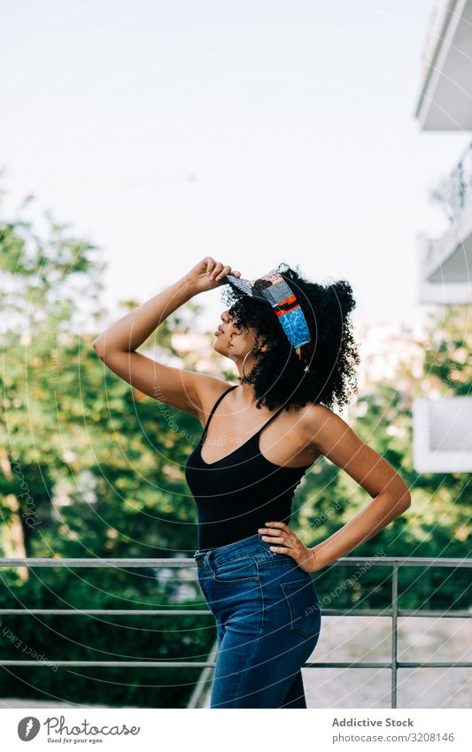 Pretty ethnic female by metal railing woman fashionable stylish trendy glamorous clothing outfit headband jeans tank top young african american casual beautiful