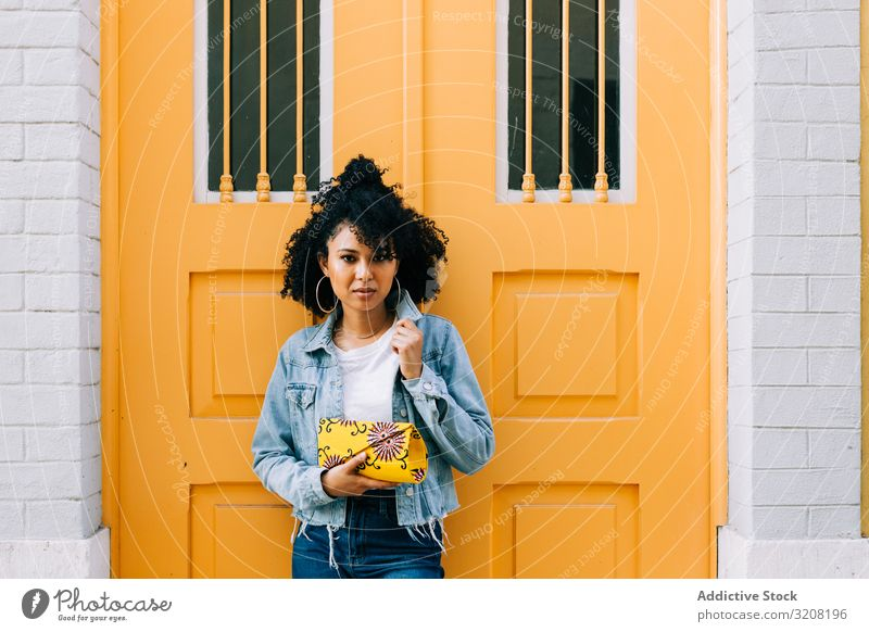 Stylish ethnic female by yellow door woman arch stylish trendy architecture travel tourism destination young african american casual pensive attractive