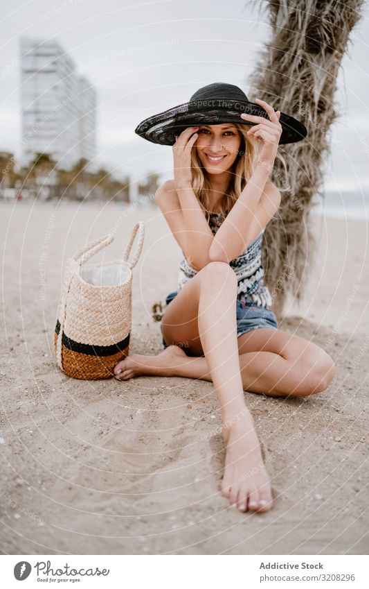 Young beautiful female relaxing on beach woman hat fashionable glamorous summer vacation travel recreation holiday resort young person attractive blonde pretty