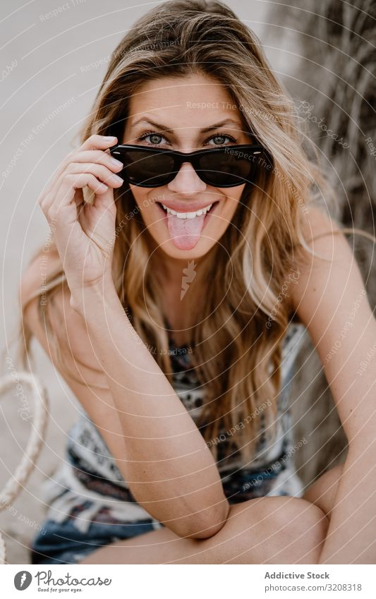 Portrait of young cheerful beautiful woman with sunglasses beach sticking out tongue fashionable funny glamorous grimace playful summer vacation travel