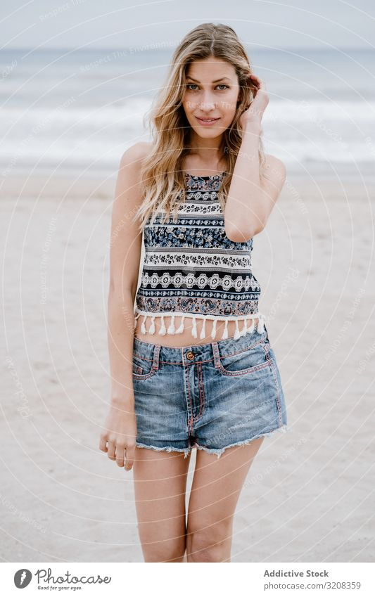 Happy female laughing on sandy beach woman happiness fashionable glamorous summer vacation travel recreation holiday resort young person attractive beautiful