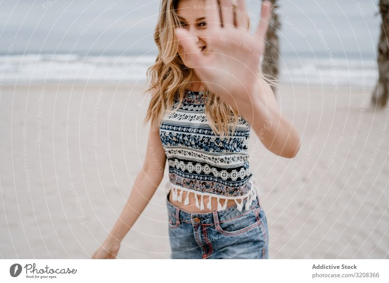 Happy female posing on sandy beach woman covering face hand happiness blocking face fashionable glamorous summer vacation holiday young person attractive