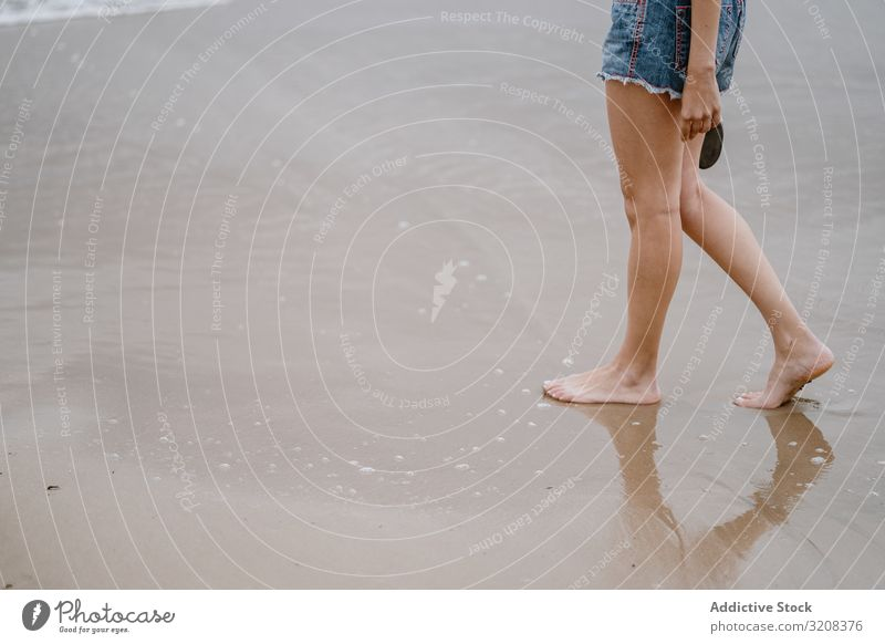 Young female walking barefoot on wet sand woman beach summer vacation travel recreation holiday joy freedom happiness young person attractive casual carefree