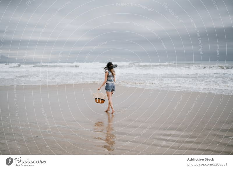 Young female walking barefoot on sandy beach woman hat bag fashionable glamorous ocean summer vacation travel recreation holiday landscape picturesque young