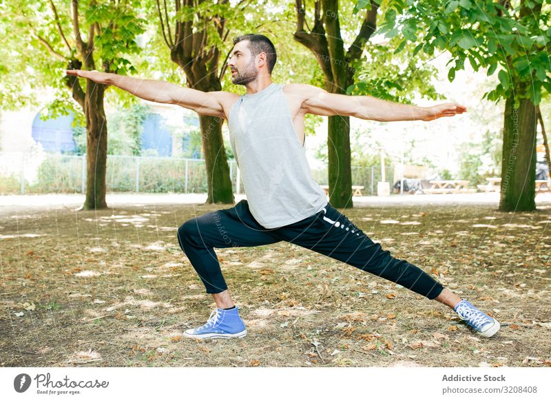Sporty man stretching up in park sportswear workout warm up athletic energy posture lifestyle focused warrior fit physical summer recreation concentrated action