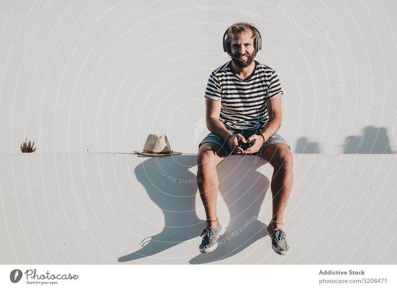 Young male sitting with smartphone and headphones man music travel vacation holiday la restinga canary island el hierro using summer young person casual bearded