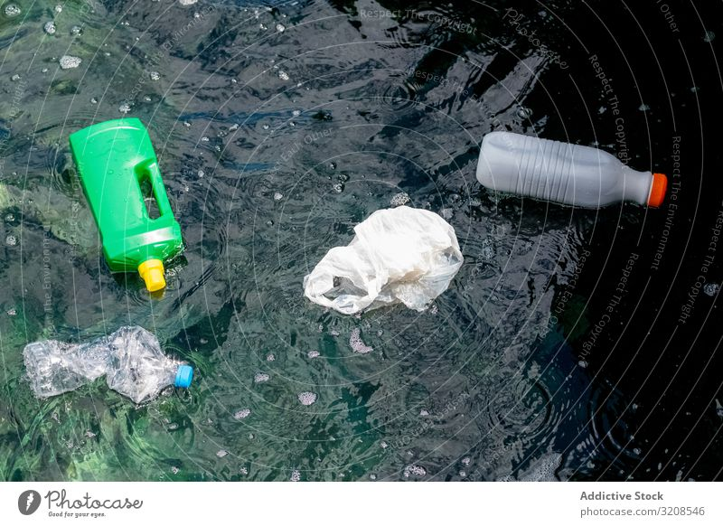 Plastic bottles and bag floating on water pollution plastic rubbish environmental ecology toxic recycling dangerous nature global world damage problem issue bio