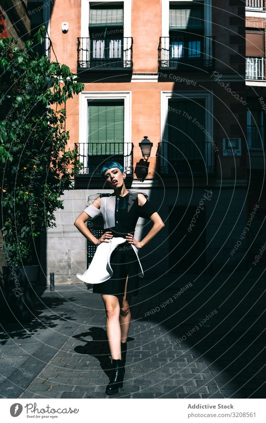 Confident lady in futuristic dress on street woman city trendy model fashion contrast confident vogue buildings pavement hands on waist young style female